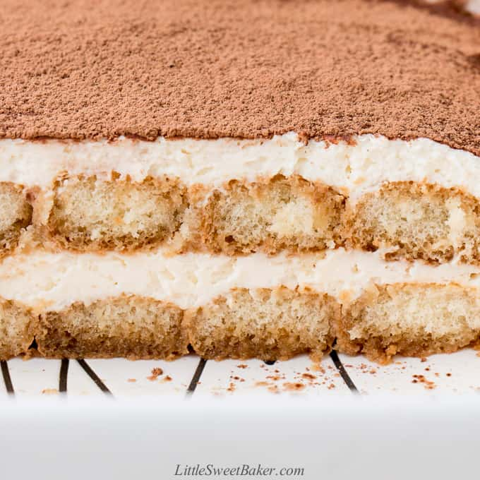 a cross section of tiramisu in a white baking pan