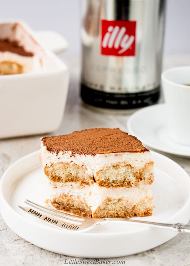A slice of eggless tiramisu with a piece missing on a white plate with a silver fork.