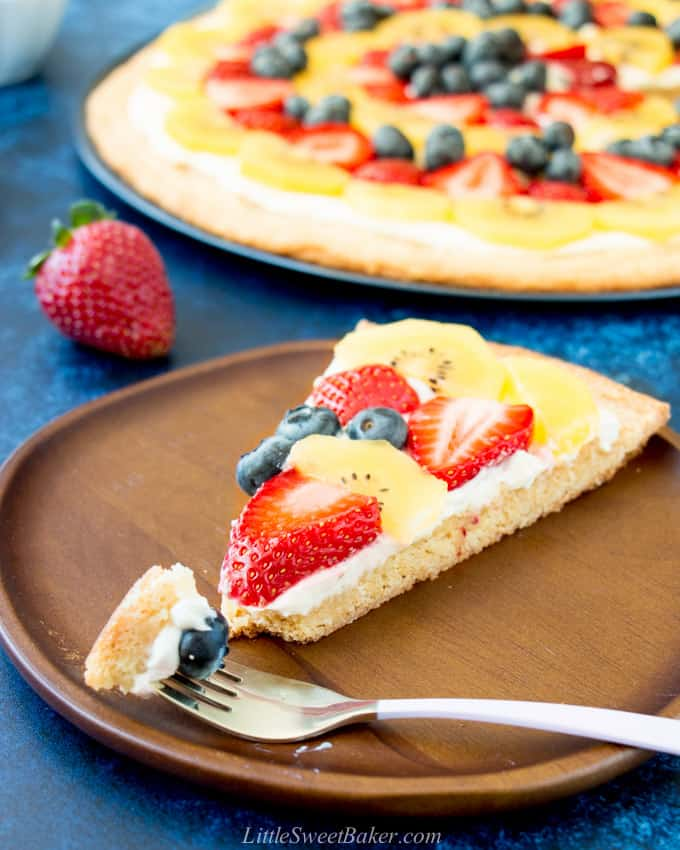 A slice of fruit pizza on a wooden place with a piece on a fork.