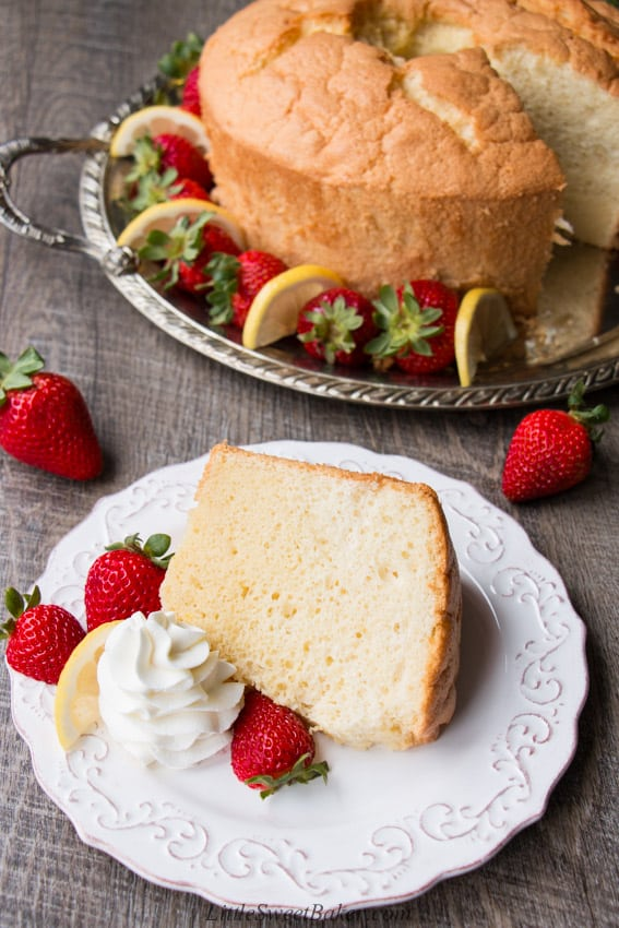 A slice of chiffon cake on a white plate with strawberries, lemon slice and whipped cream.