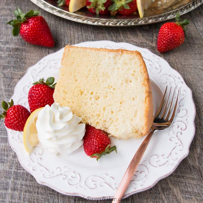 A slice of chiffon cake on a white plate with strawberries, whipped cream and a copper fork.