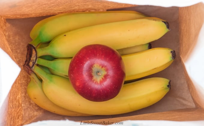 A bunch of bananas in a paper bag with a red apple.