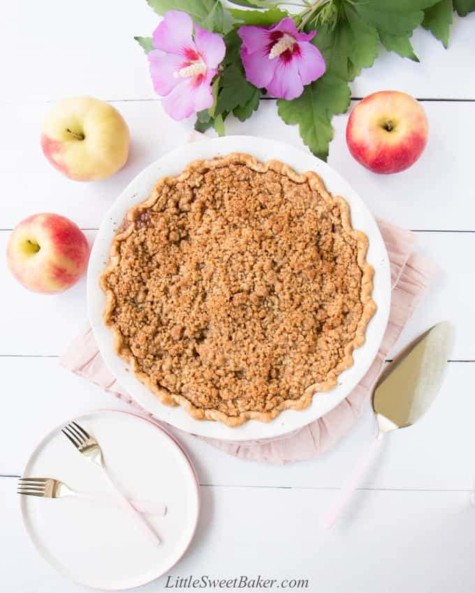 A Dutch apple pie on a pink napkin surrounded by flowers, apples, plate, and forks.