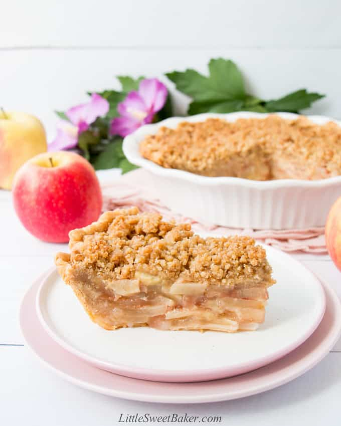 A slice of Dutch apple pie on a white and pink plate.