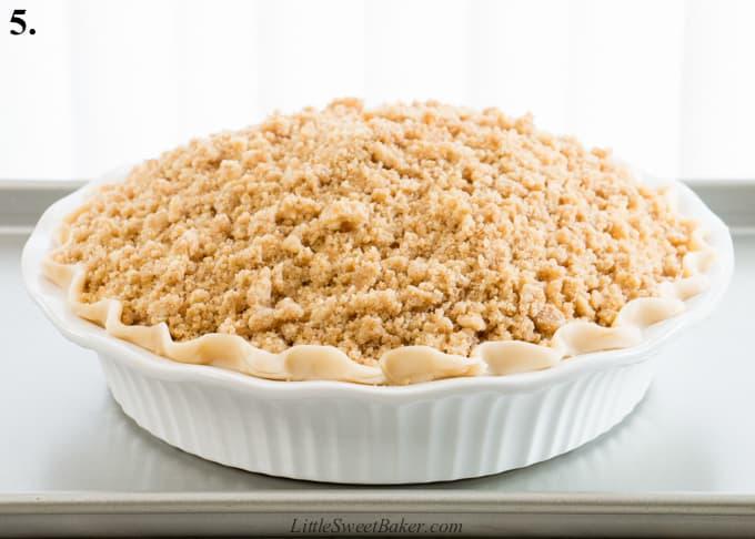 An unbaked Dutch apple pie on a baking sheet.