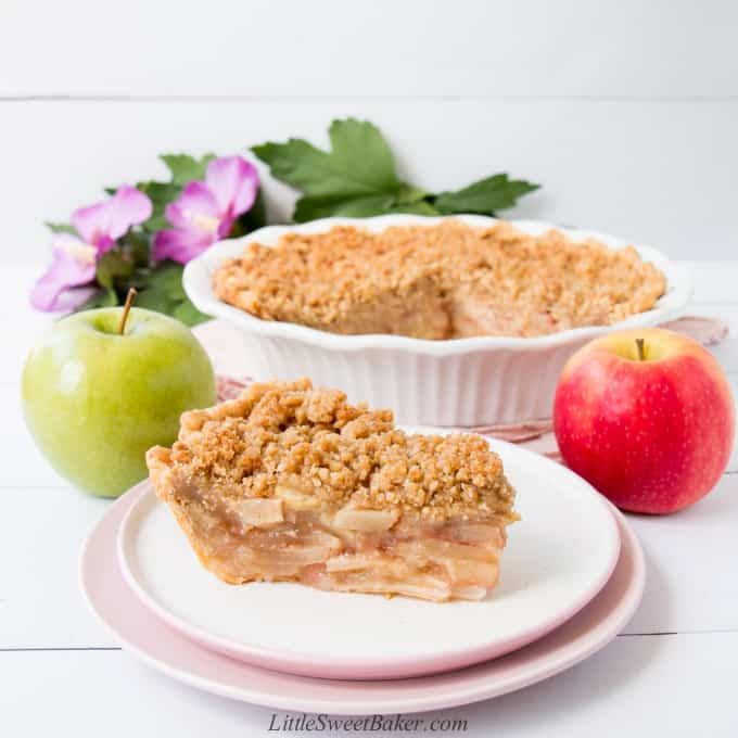A slice of dutch apple pie on a white and pink plate with apples, the rest of the pie and flowers in the background.