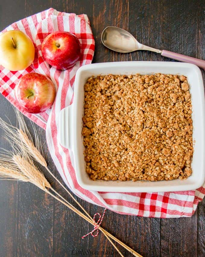 An apple crisp on a red and white dish towel surrounded by apples.