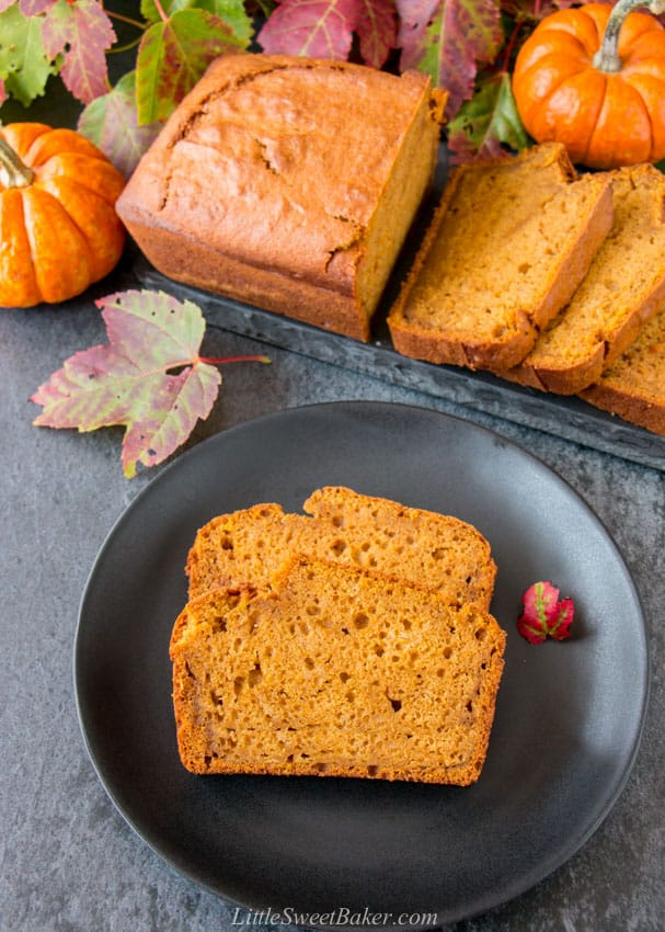 Two slices of pumpkin bread on a black plate with the rest of the loaf behind it.