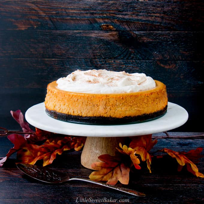 A pumpkin cheesecake on a marble cake stand with a dark wood background and fall leaves.
