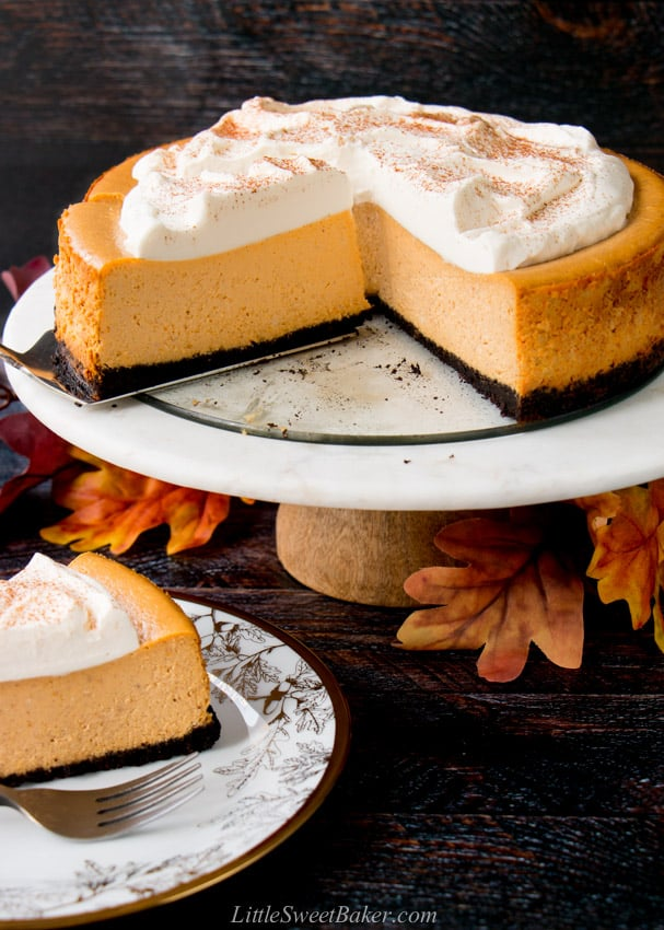 A pumpkin cheesecake on a marble cake stand with a few slices cut.