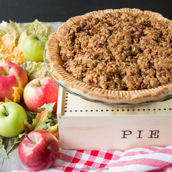 An apple crumble pie on top of a pie box surrounded by apples.