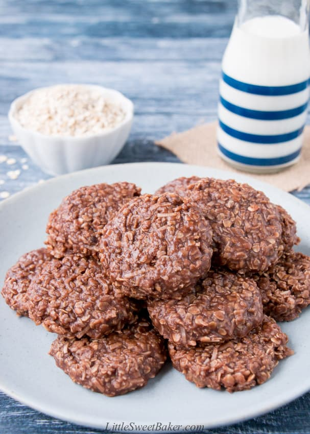 A plate of no-bake cookies with a glass of milk and rolled oats in the background.