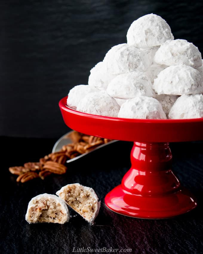 snowball cookies on a red dessert stand with pecans in the background.