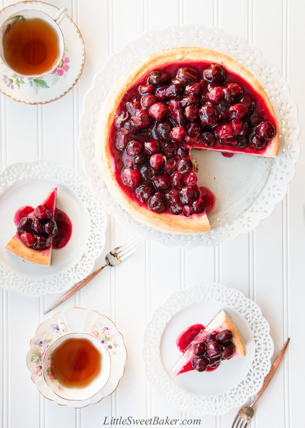An overhead view of a cherry cheesecake and two slices on serving plates.
