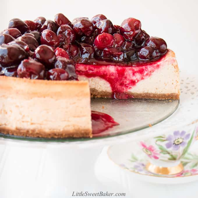 A cherry cheesecake on a white cake stand with a slice cut out.