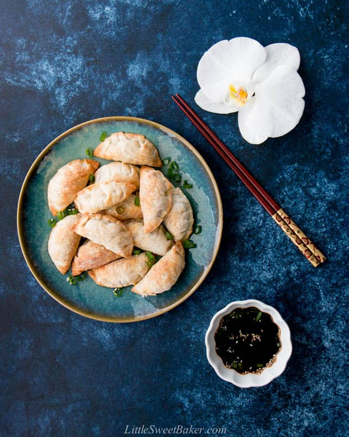 A plate of baked Chinese dumpling surrounded by a pair of chopsticks, soya sauce and a white orchid.