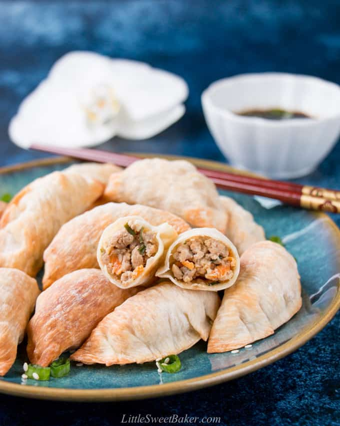 A plate of baked Chinese dumplings with one cut in half to show the filling.
