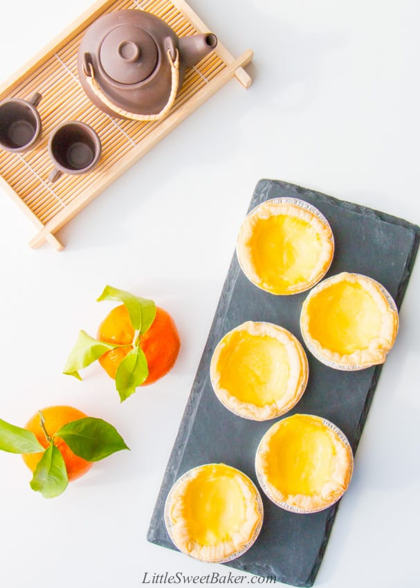 Chinese egg tarts on black late with mandarins and tea serving tray.