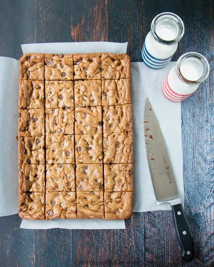 A tray of chocolate chip cookie bars cut into squares surrounded by a knife and two glasses of milk.