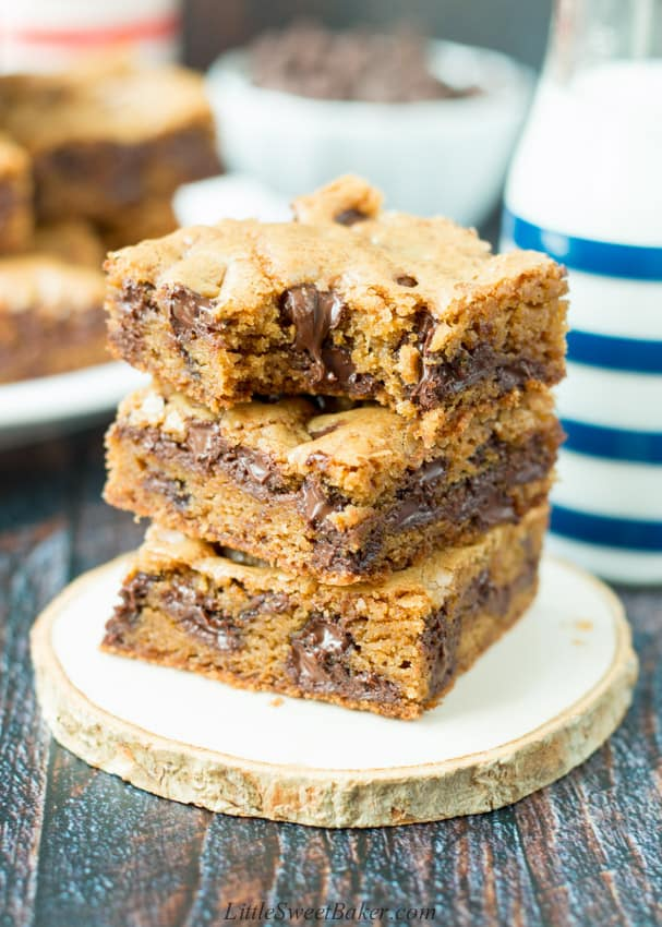 A stack of chocolate chip cookie bars with a bite taken out of the top one.