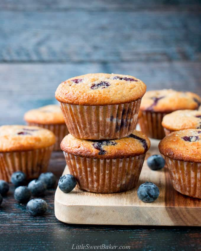 Healthy blueberry muffins with fresh blueberries around them.