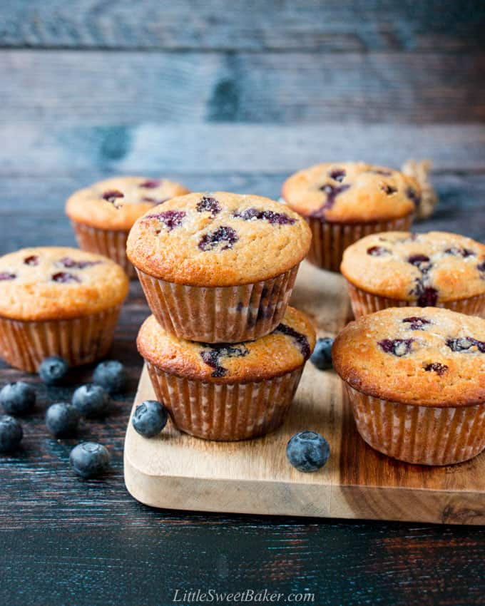 Healthy blueberry muffins on a wooden board with blueberries scattered.