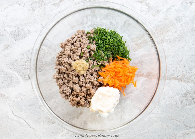 A mixing bowl of cooked ground turkey, chives, carrots, mayonnaise and ginger.
