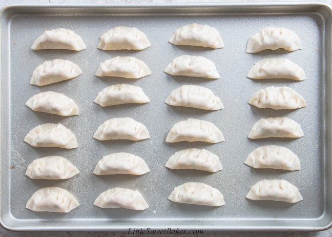a pan of Chinese dumplings ready to be baked