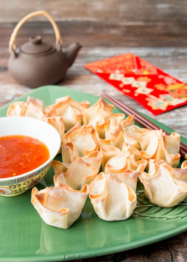 A plate of baked turkey rangoon with dipping sauce and a pair of chopstick.