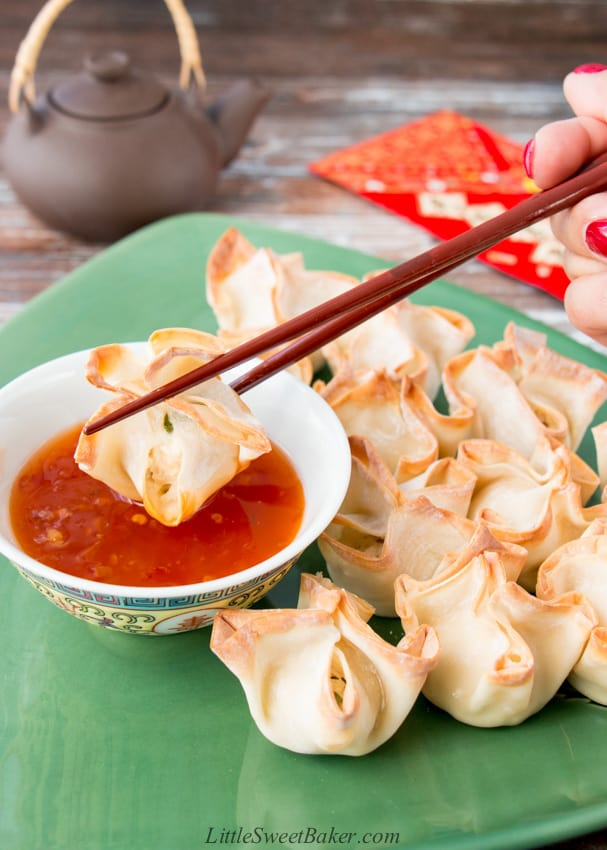 A plate of baked turkey rangoon with one being dipped in sweet chili sauce.