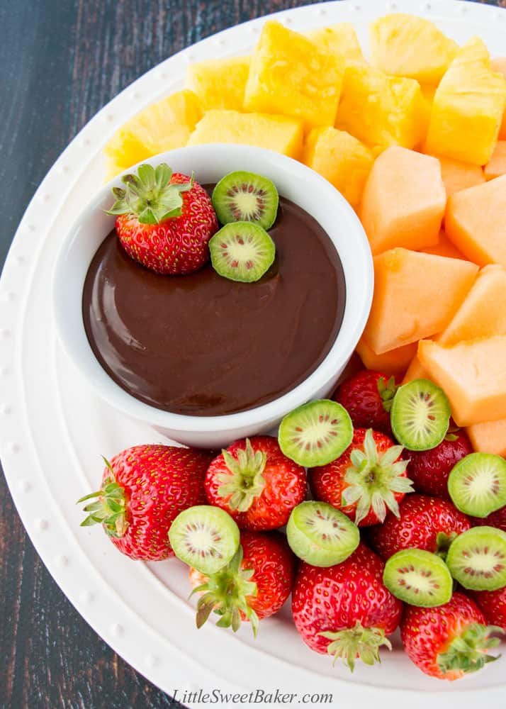 A white plate of strawberries, cantaloupe and pineapple chunks with chocolate ganache dip.