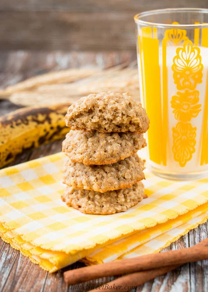 A stack of banana oatmeal cookies on a yellow napkin with a glass of milk and cinnamon sticks.
