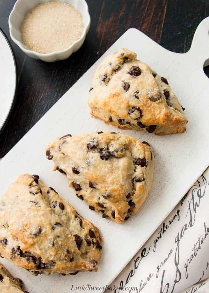 Chocolate chip scones on a white wooden board.