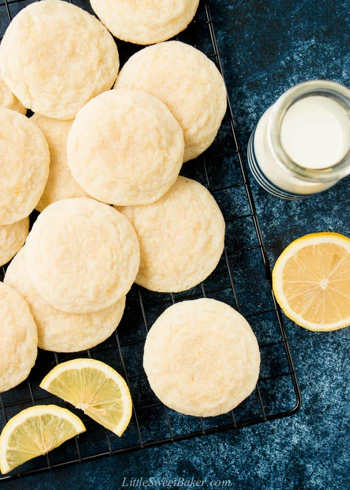 Lemon sugar cookies on a cooling rack with lemons and a glass of milk.