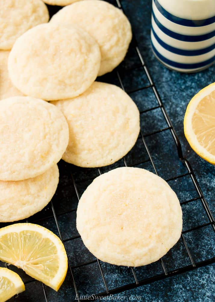 Lemon cookies on a cooling rack with some lemon wedges and a glass of milk.