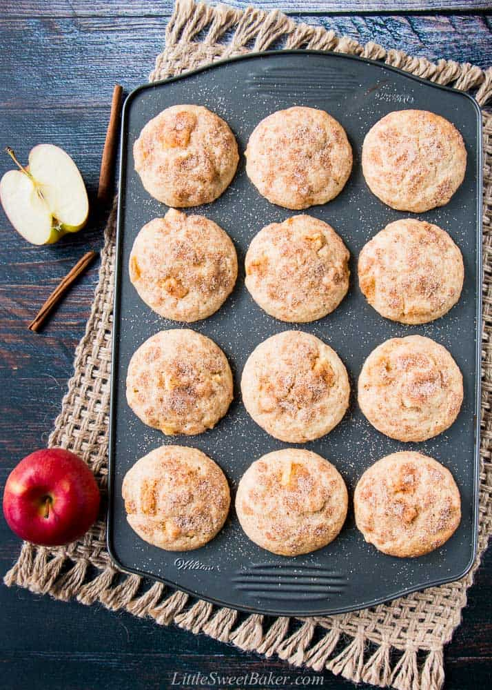 A muffin pan of apple cinnamon muffins on a burlap mat with apples apples and cinnamon sticks
