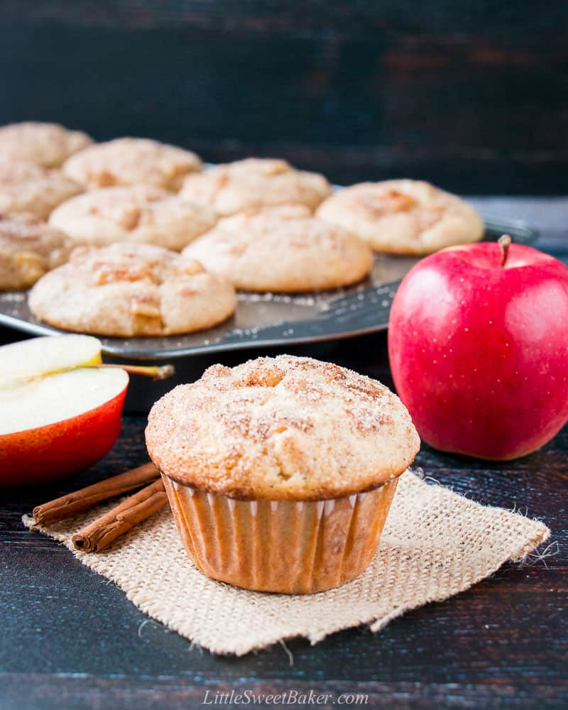 An apple cinnamon muffin in a piece of burlap with two cinnamon sticks, red apples and muffin pan in the background.