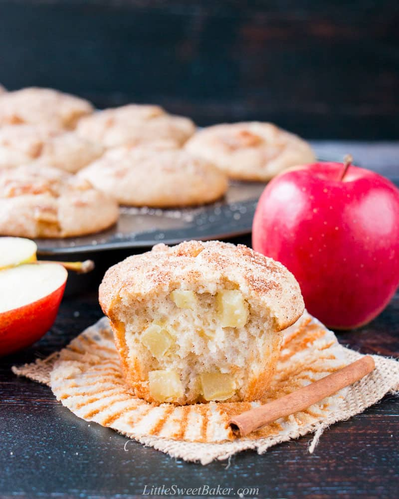 An apple muffin with a big bite taken out to show the inside texture with a cinnamon stick, apples, and muffin pan in the background.