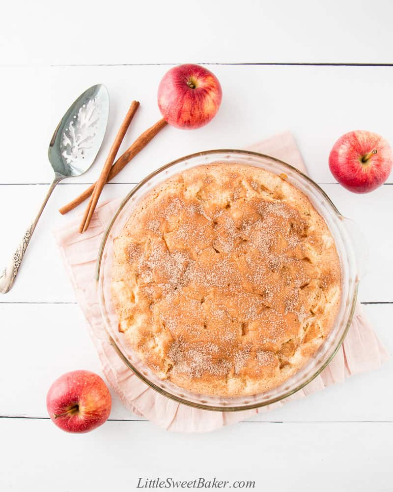 A cinnamon sugar apple cake on a pink ruffled cloth surrounded by apples and cinnamon sticks.