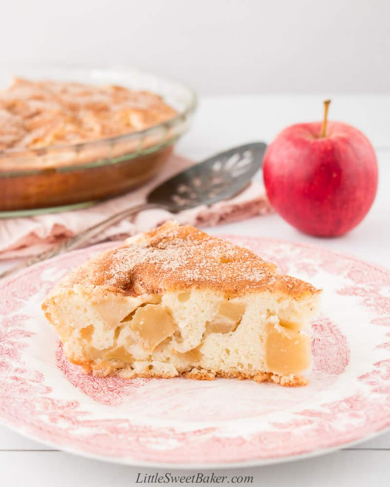 A slice of apple cinnamon cake on vintage plate with an apple and rest of cake in the background.