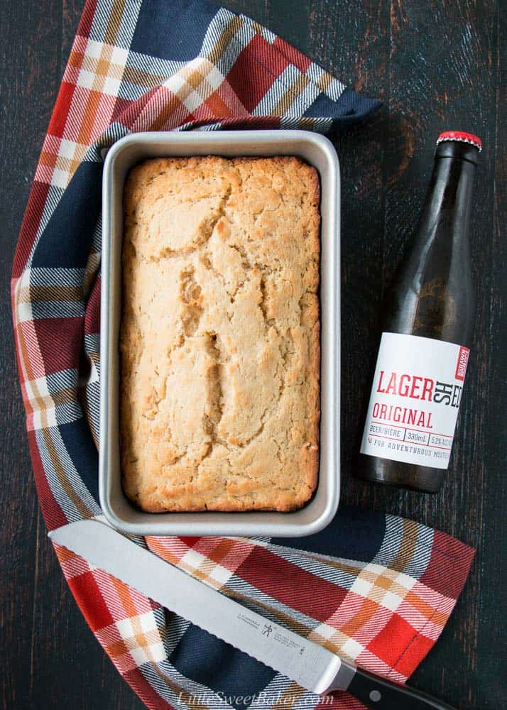 A loaf of beer bread in a baking pan with a plaid kitchen tower and bottle of lager.
