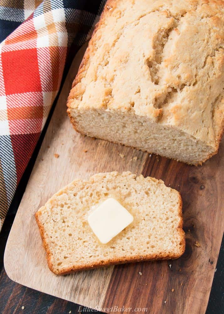 A loaf of beer bread on a cutting board with a pat of butter on a slice.
