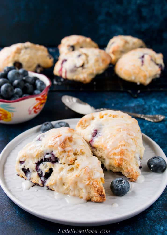 Two glazed blueberry scones on a grey plate.