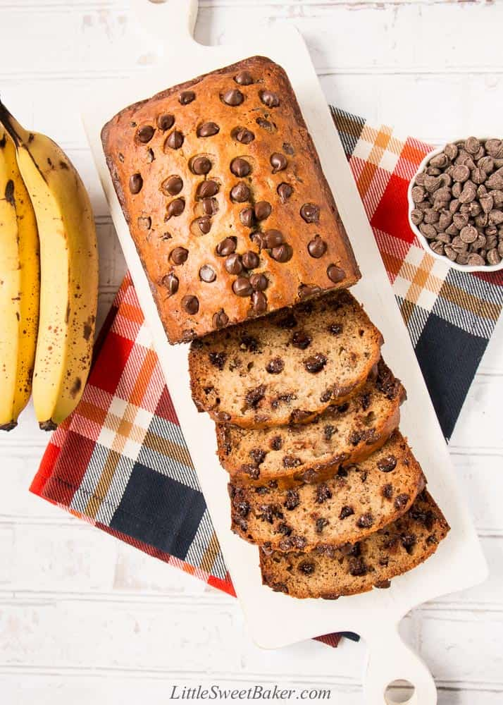 Chocolate chip banana bread on a white cutting board with a few slices cut.