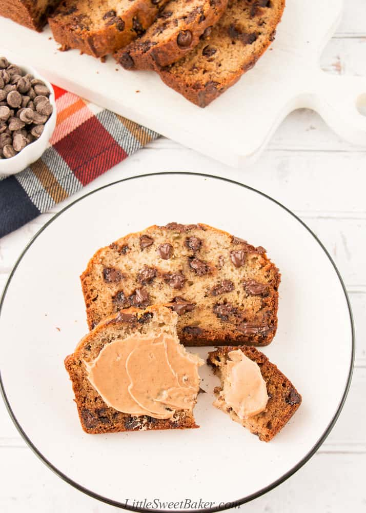Two slices of chocolate chip banana bread on a white plate with some peanut butter on the one slice.