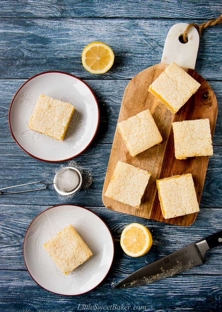 Two lemon bars in a gray and five lemon bars on a wooden cutting board.