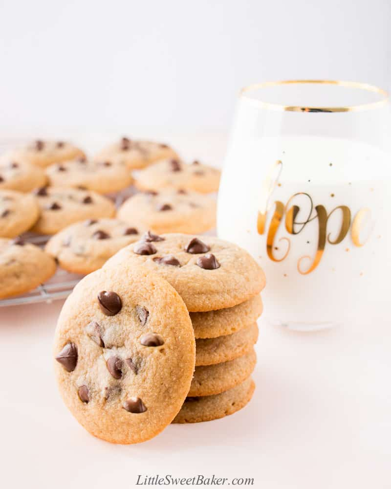 A stack of chocolate chip cookies with a glass of milk.