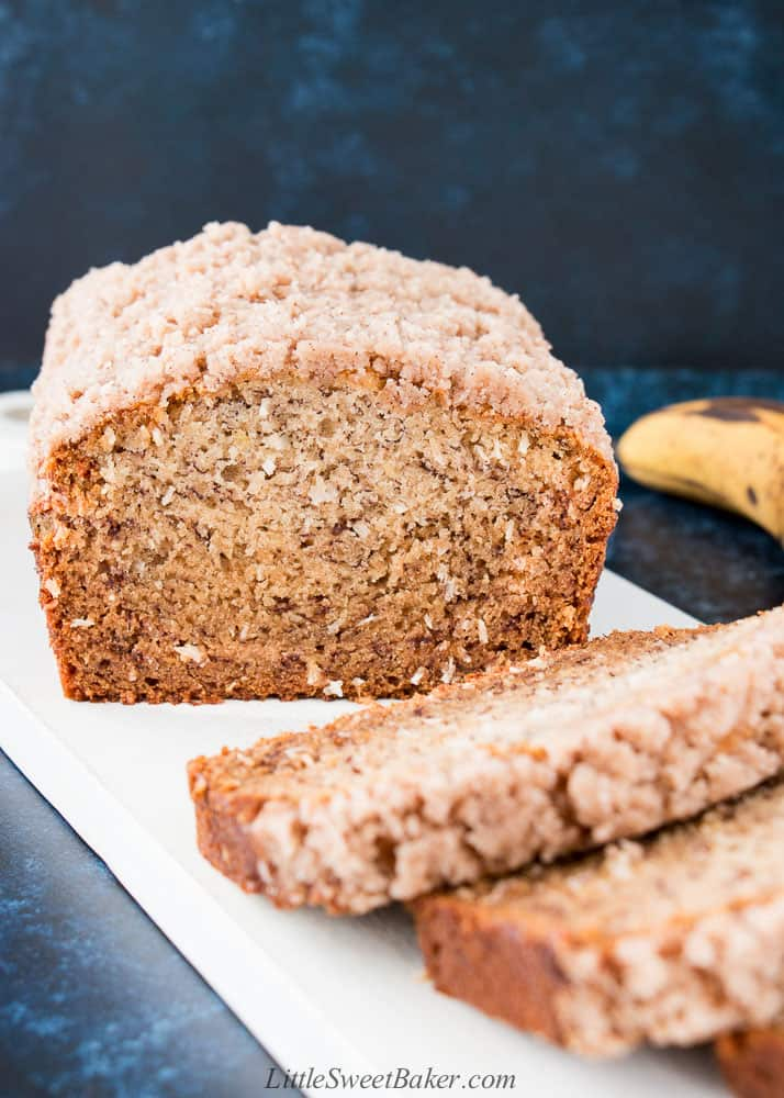 A loaf of vegan banana bread with crumb topping on a white wooden board.