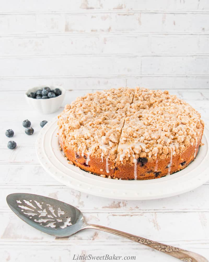 A whole blueberry crumb cake on a white plate.