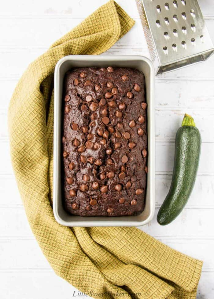 A loaf of chocolate zucchini bread with a green dish towel, zucchini and grater around it.